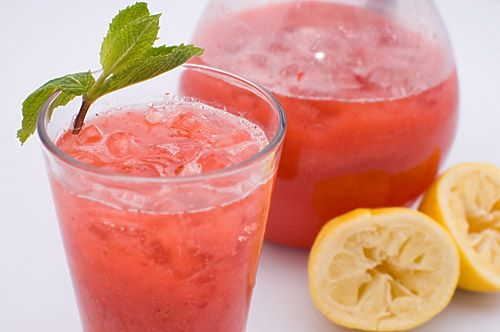 6 lemons  1 to 1 1/2 cups simple syrup   1 (16 ounce) container strawberries, hulled and halved  1 quart sparkling water  ice cubes  mint for garnish