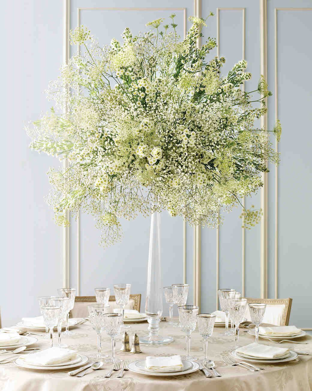 SPRAY CENTERPIECE Miniature daisies, doily-shaped Queen Anne's lace, and baby's breath come together in a beautiful balancing act atop a tall, graceful candlestick. Elegant and Inexpensive Wedding Flower Ideas   Martha Stewart Weddings