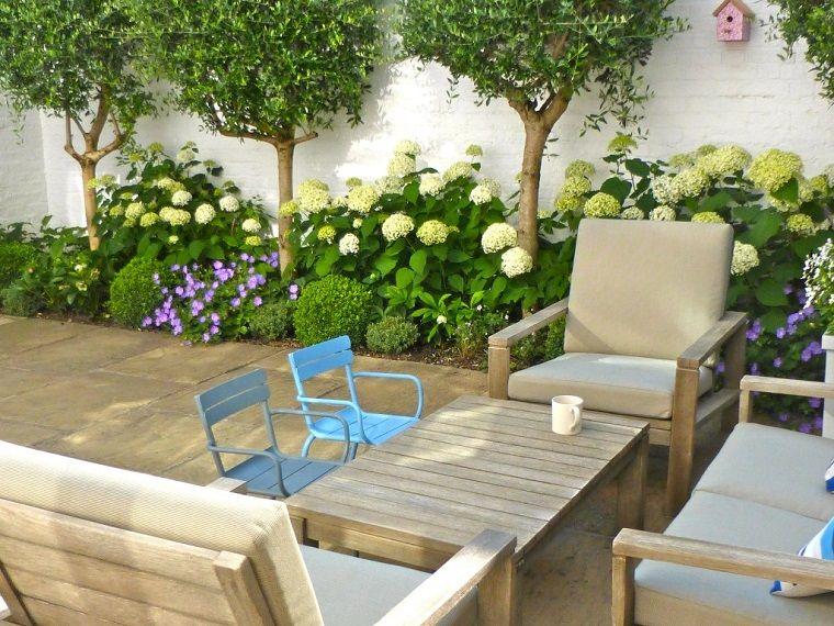Giardino piccolo con un arredamento di legno con tavolino basso e