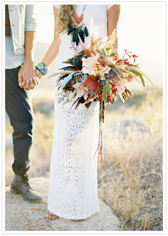 Beautifully bohemian. Laser cut white gown, eclectic bangles, feathered necklace and a gorgeous boho bouquet.