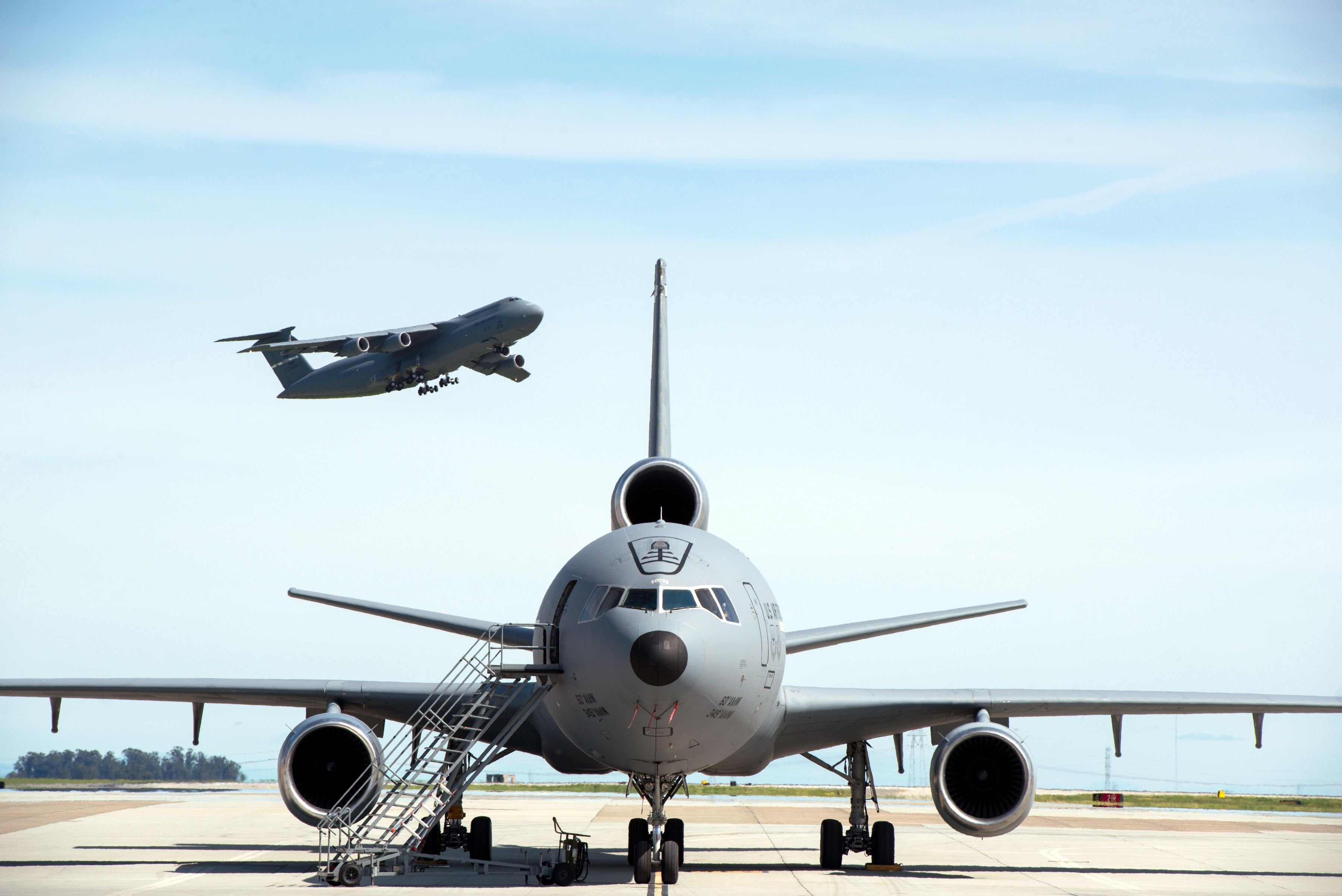 A KC-10 Extender is parked on the ramp as a C-5M Super ...