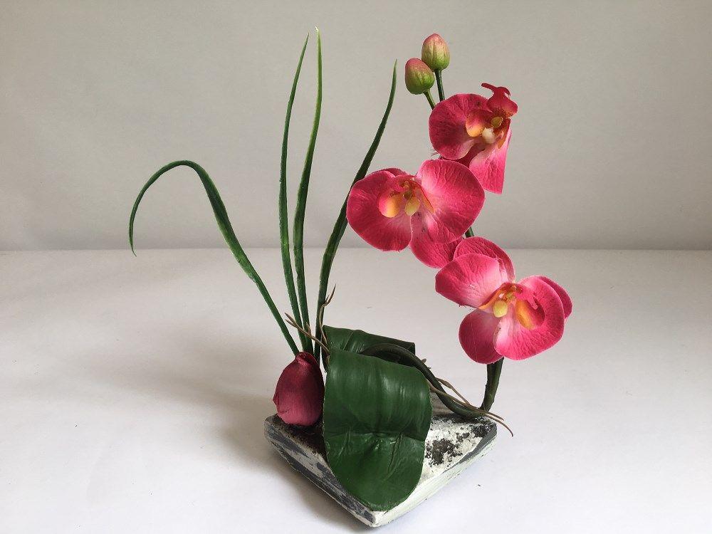 Composition florale artificielle orchidee sur pierre.