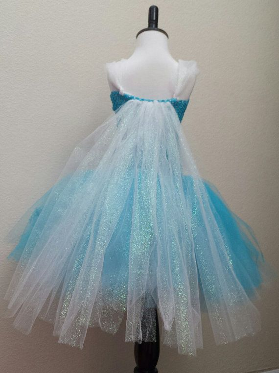 Frozen Elsa Inspired Tutu Dress This beautiful tea length inspired tutu dress is made with turquoise and white tulle with snowflakes. The glittered tulle cape is attached to the back of the dress. Tur