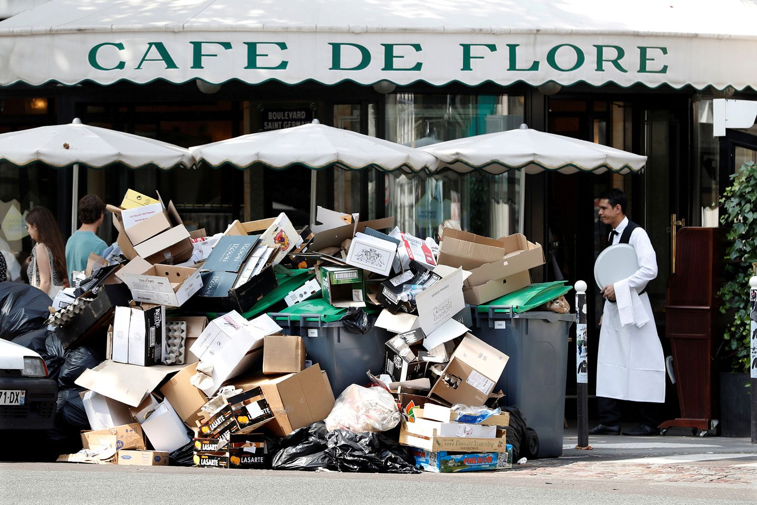 A waiter stands near a pile of trash bags in front of the Cafe de Flore in Paris during a garbage-collector and sewer-worker strike in Paris to protest the labor reforms law proposal, on June 8, 2016.