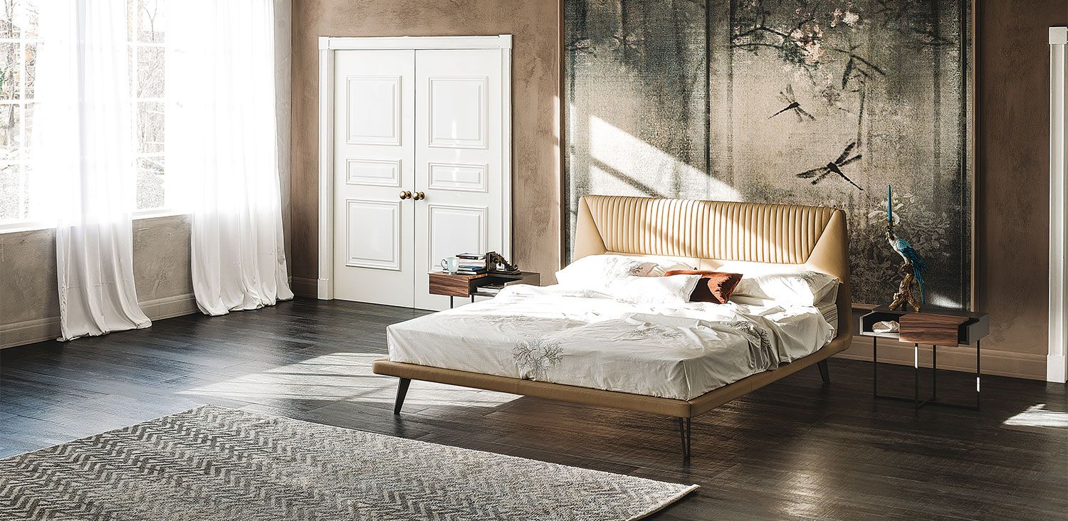 Upholstered bed covered in synthetic leather or soft leather as per sample card. With matt bronze (OP15), white (GFM71) or graphite (GFM69) embossed lacquered steel feet. Optional: back headboard covered in soft leather or leathertex. Slats included.