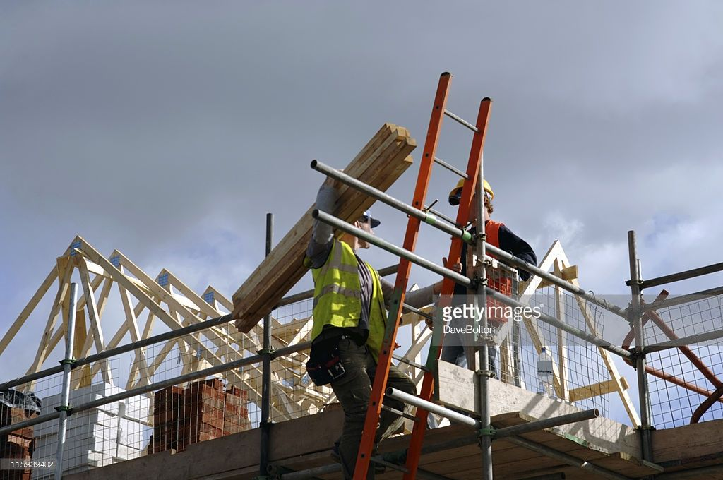 A Pair Of Roofers Working On A Construction Site In Manchester England No Sharpening In Camera Or Pp Apprenticeship Painting Gutters Construction