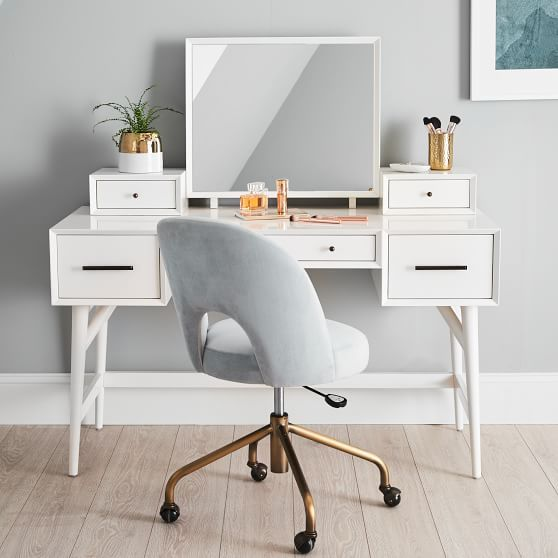 Inspired by modern American design, this set borrows its slim legs and rounded, beveled edges from iconic '50s and '60s furniture silhouettes. Made with a generous tabletop and spacious drawers, it keeps all of your essentials neatly organized in style. The vanity topper is removable so you can transform your get-ready station into a study space. Designed in collaboration with West Elm.   GREENGUARD Gold Certified. This low-emitting product has been tested for more than 10,000 chemicals and VOCs to contribute to cleaner indoor air.  Learn more. All wood is sustainably sourced and FSC®-certified.  Learn more. Acorn finish is expertly crafted from eucalyptus wood, MDF with acacia veneer and sap gum. White finish is expertly crafted from sap gum and MDF. Pebble finish is expertly crafted from ash wood, MDF with ash veneer and sap gum. Water-based finish that meets stringent chemical emission standards. Vanity is designed with a mirror and 2 drawers with bronze-finished metal hardware. Masterfully crafted with mortise-and-tenon construction and frame-and-panel joinery for structural integrity. The use of veneers results in high-quality furniture with flawless surfaces and consistent color tones. Adjustable levelers provide stability on uneven floors. Rigorously tested to meet or exceed all required and voluntary safety standards. Vanity can only mount to our Mid-Centry Desk. We use medium density fiberboard for structural integrity and sustainability. Imported.