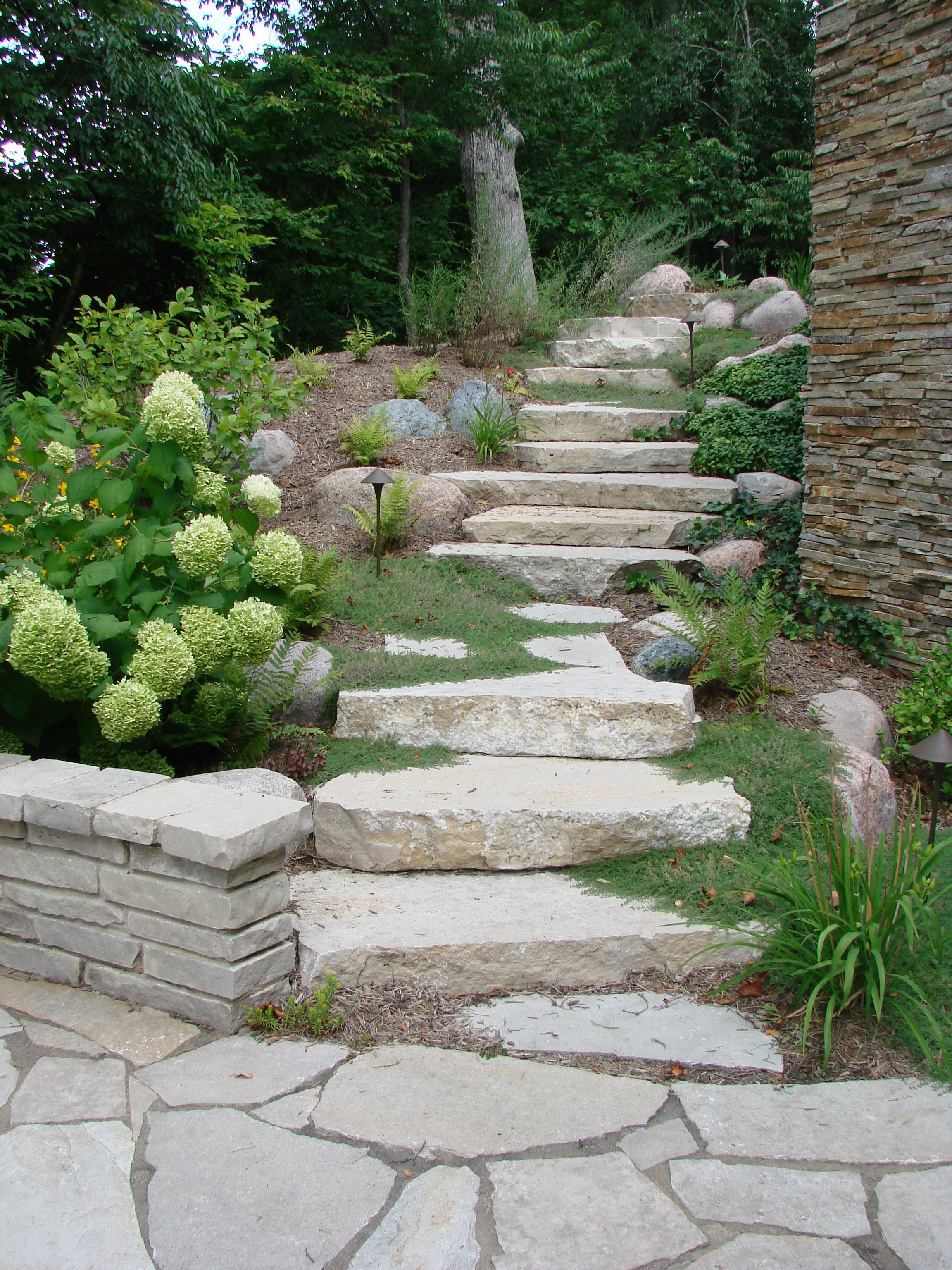 The natural stone steps of a stairway garden feature climb a small - Outcropping Stone Steps Stuber Land Design