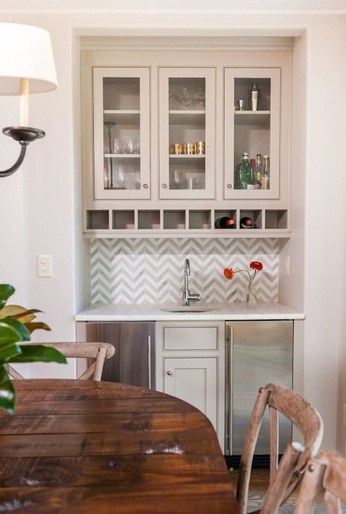 Dining Room Alcove Is Filled With A White And Gray Marble Chevron Tiled Backsplash Above Cabinets Topped Countertop Framing Round Bar Sink