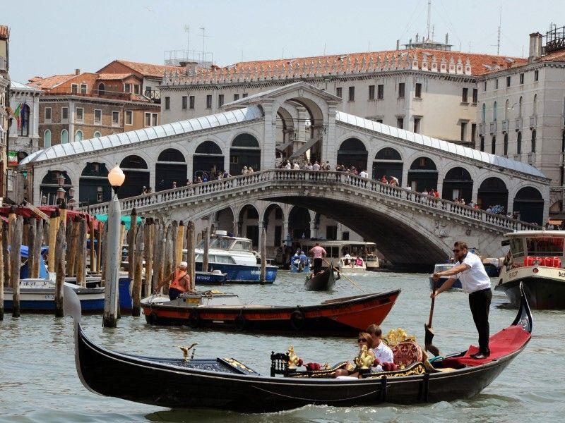Gondeln, Boote und ein Vaporetto fahren auf dem Canale Grande vor der Rialtobrücke in Venedig