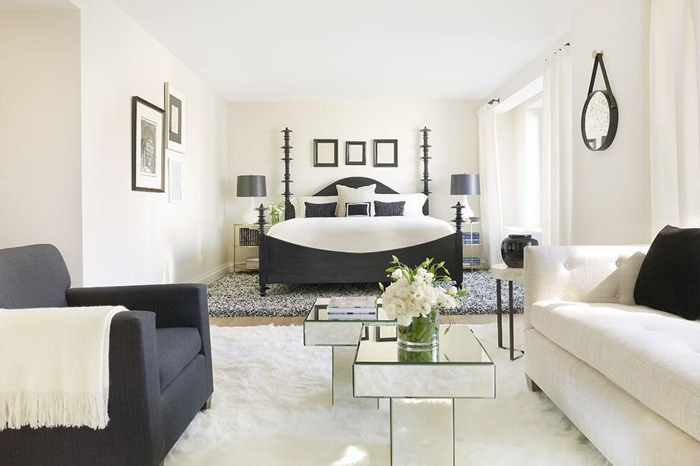 l shaped bedroom in black and white decor walls are white bed frame is black with white covering