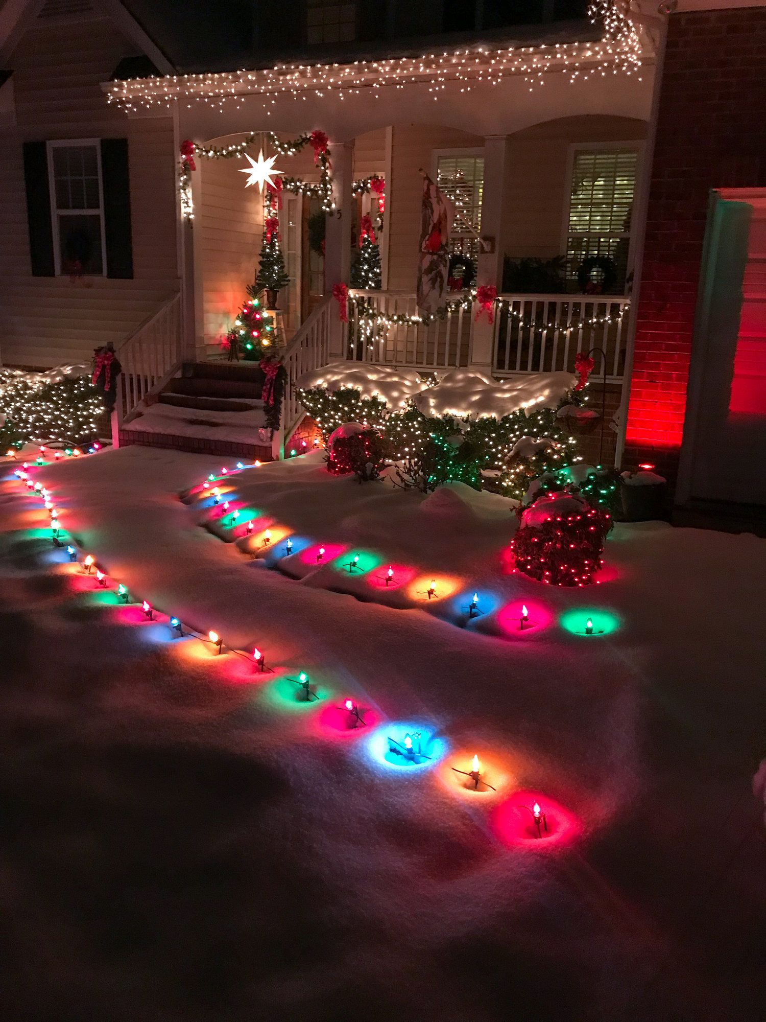 Colorful Outdoor Christmas Lights Showing Off In The Snow Outdoor Christmas Decorations Lights Christmas House Lights Decorating With Christmas Lights