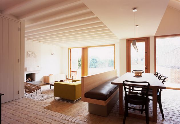 Open but separate. My ideal beautifully informal kitchen/diner... cleverly sunken, full height windows, exposed beams, pale wood  banquette dividing.