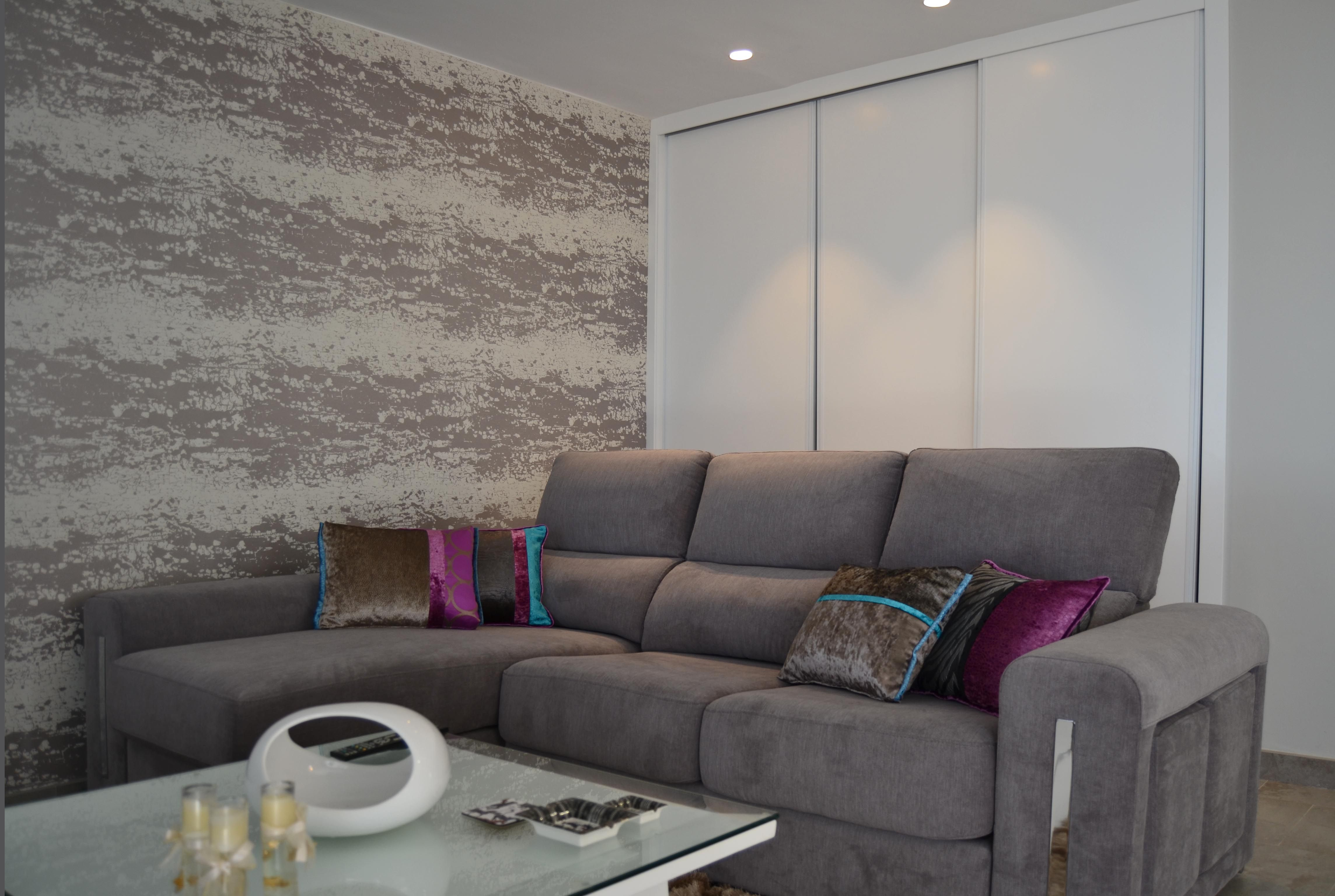 Un sofá chaise longue con cojines de distintas texturas y colores ...