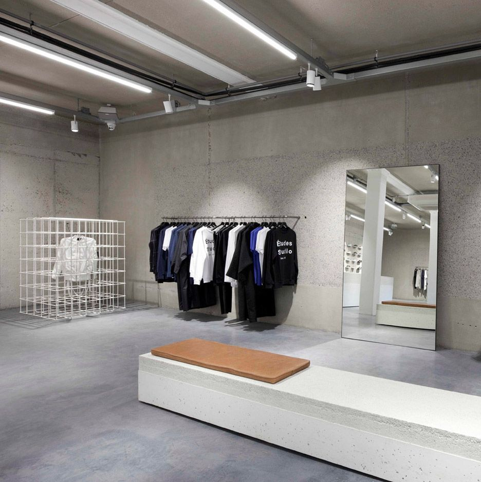 Studio Jos van Dijk transformed a canalside shop in Amsterdam into a multi-brand store for footwear label ETQ, adding a sneaker-lined wall, white metal display cages and heavy concrete furniture.