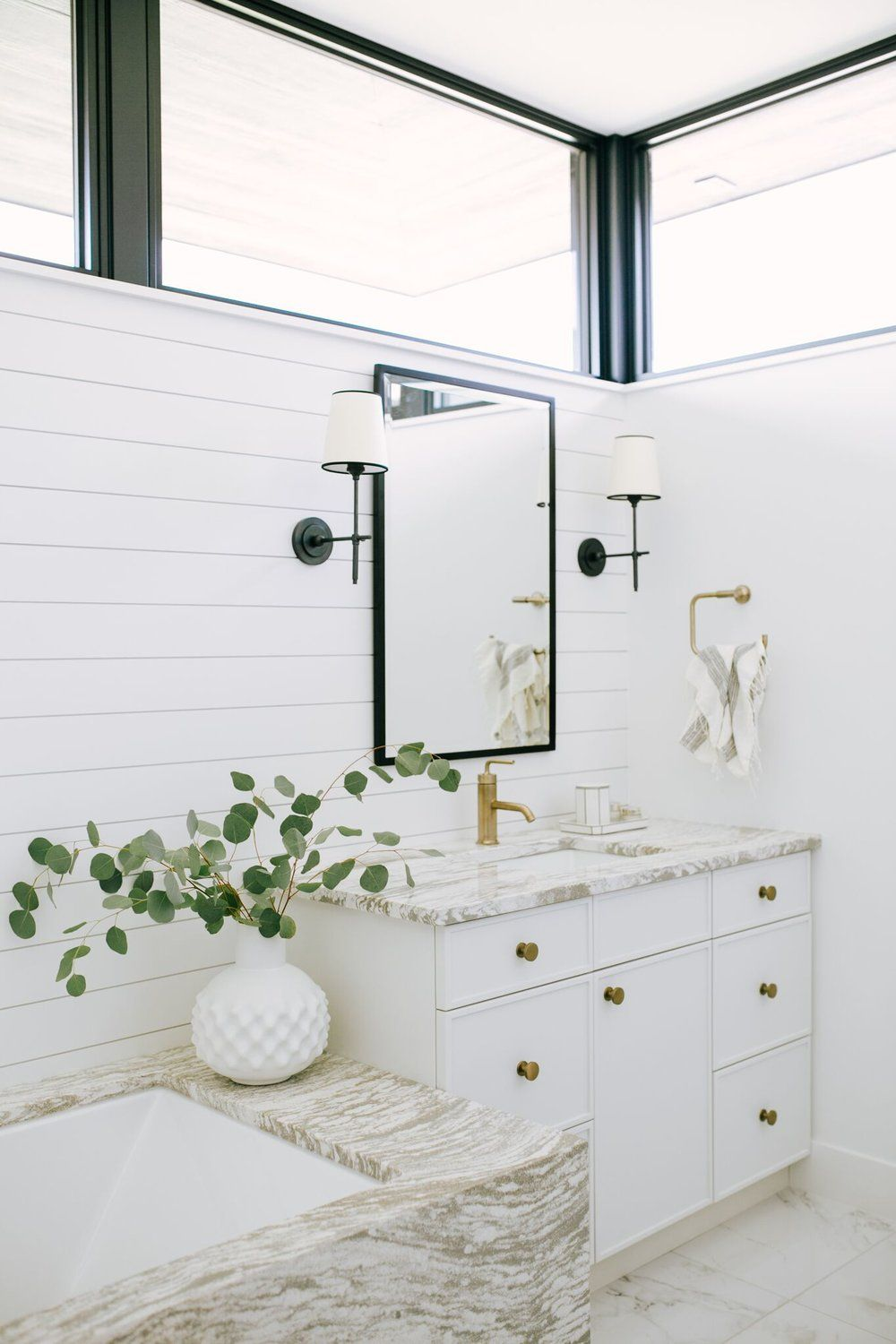 Bathroom design featuring white and tan marble and shiplap walls ...