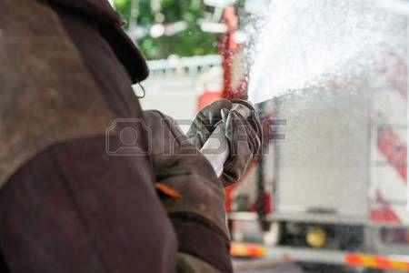 Imagen recortada de bombero pulverización de agua durante la práctica en el parque de bomberos Foto de archivo