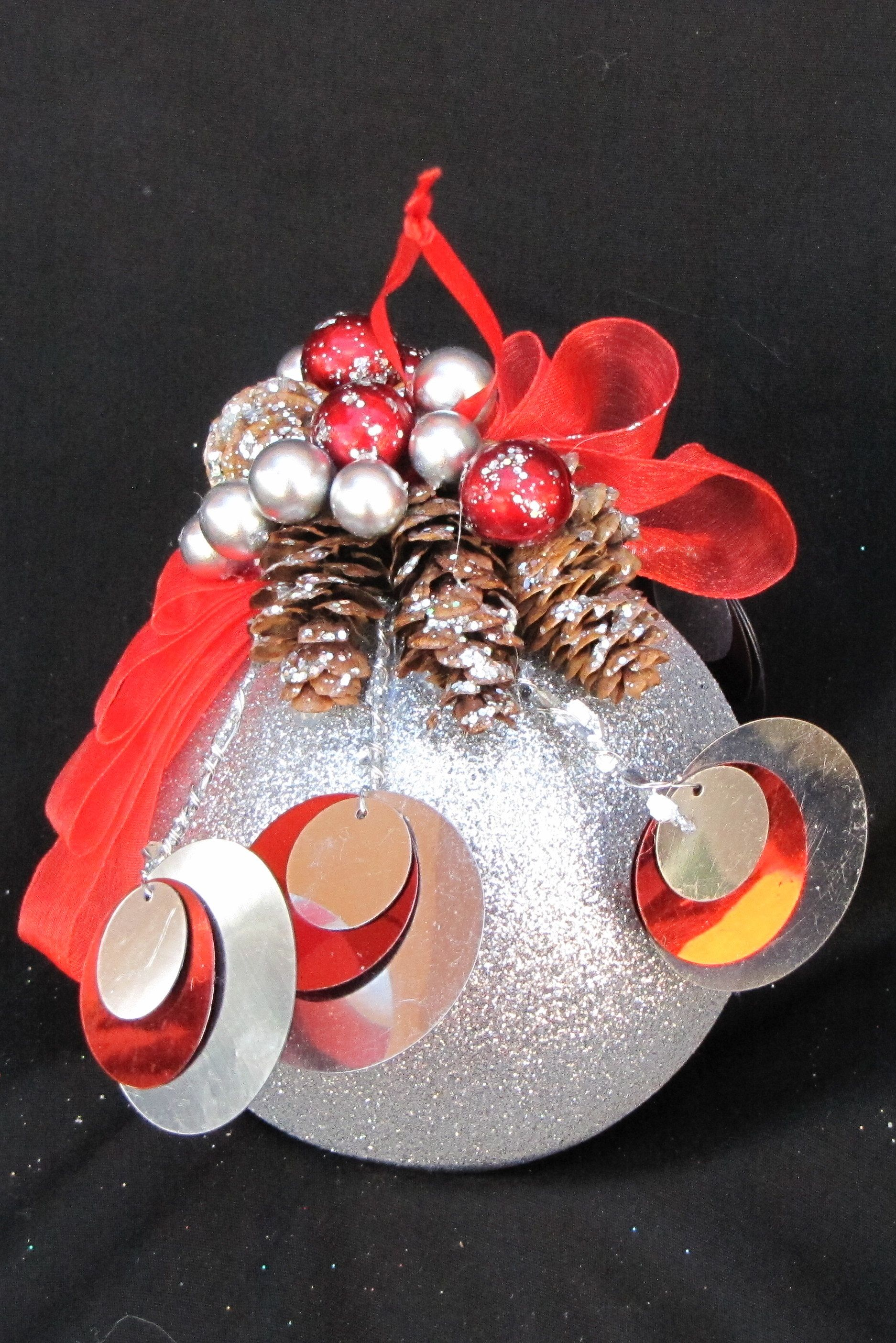 Silver ornament decorated with pine cones and miniature ornaments