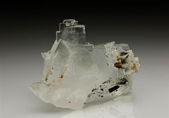 Colourless gemmy Fluorite forming a stepped tower of crystals developed from a large blocky Fluorite crystal, with some associated dark brown Goethite. From the Clara Mine, Germany.