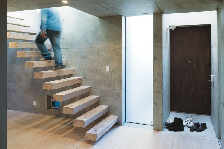 open plan concrete home in japan entryway. Tsutsui continued the Oregon pine from the floor to the steel-reinforced cantilevered staircase, which appears to float above the floor.