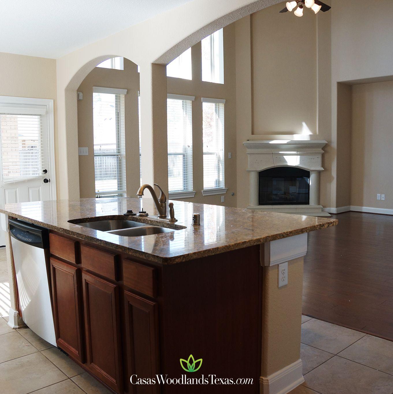 La cocina cuenta con isla con gabinetes de madera y encimeras de ...
