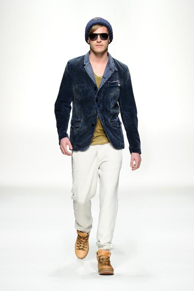 Que tiene en los pantalones vaqeros blanos, zapatos de color caqui, camisa de color amarillento sombrero azul y una chaqueta de mezchilla azul.