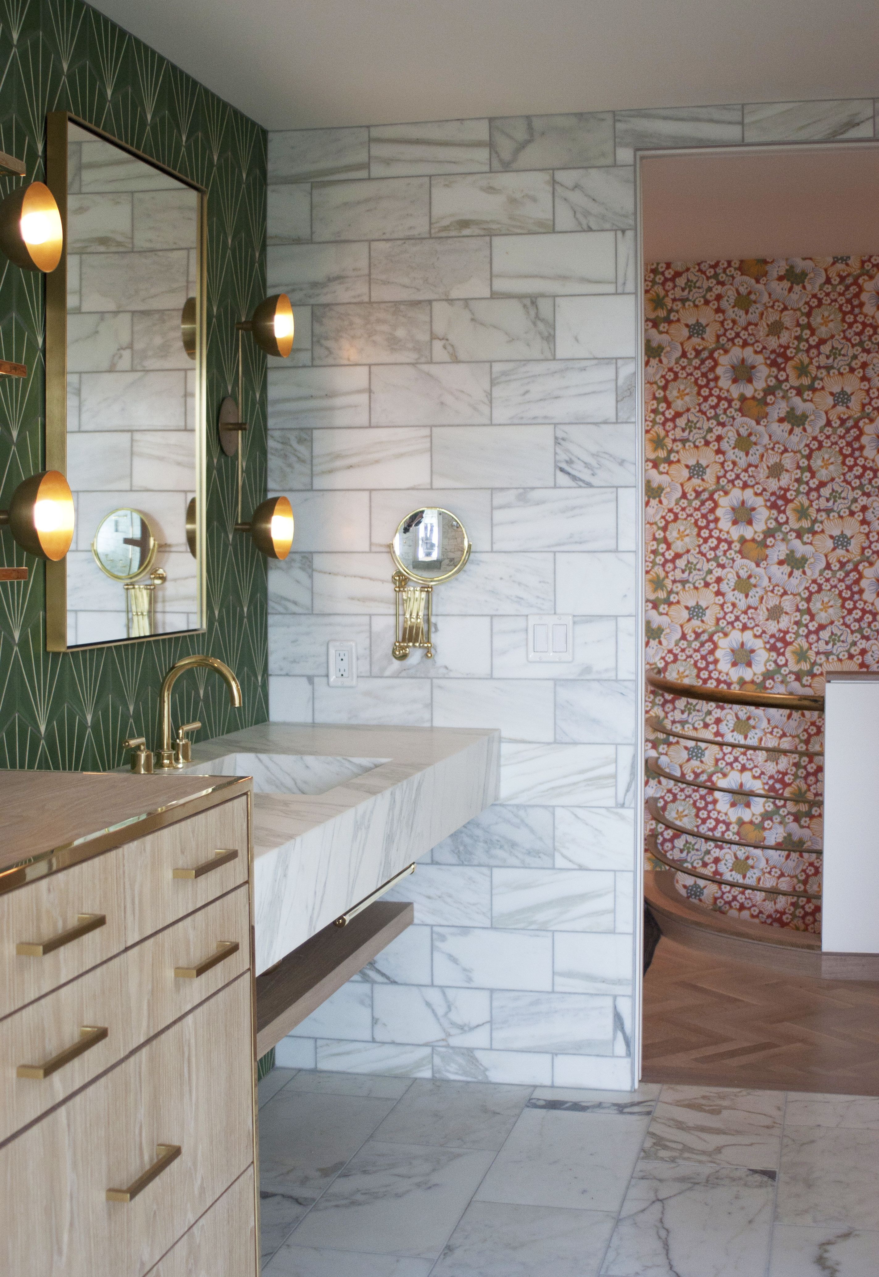 Marble, green cement tiles, wallpaper and brass is a