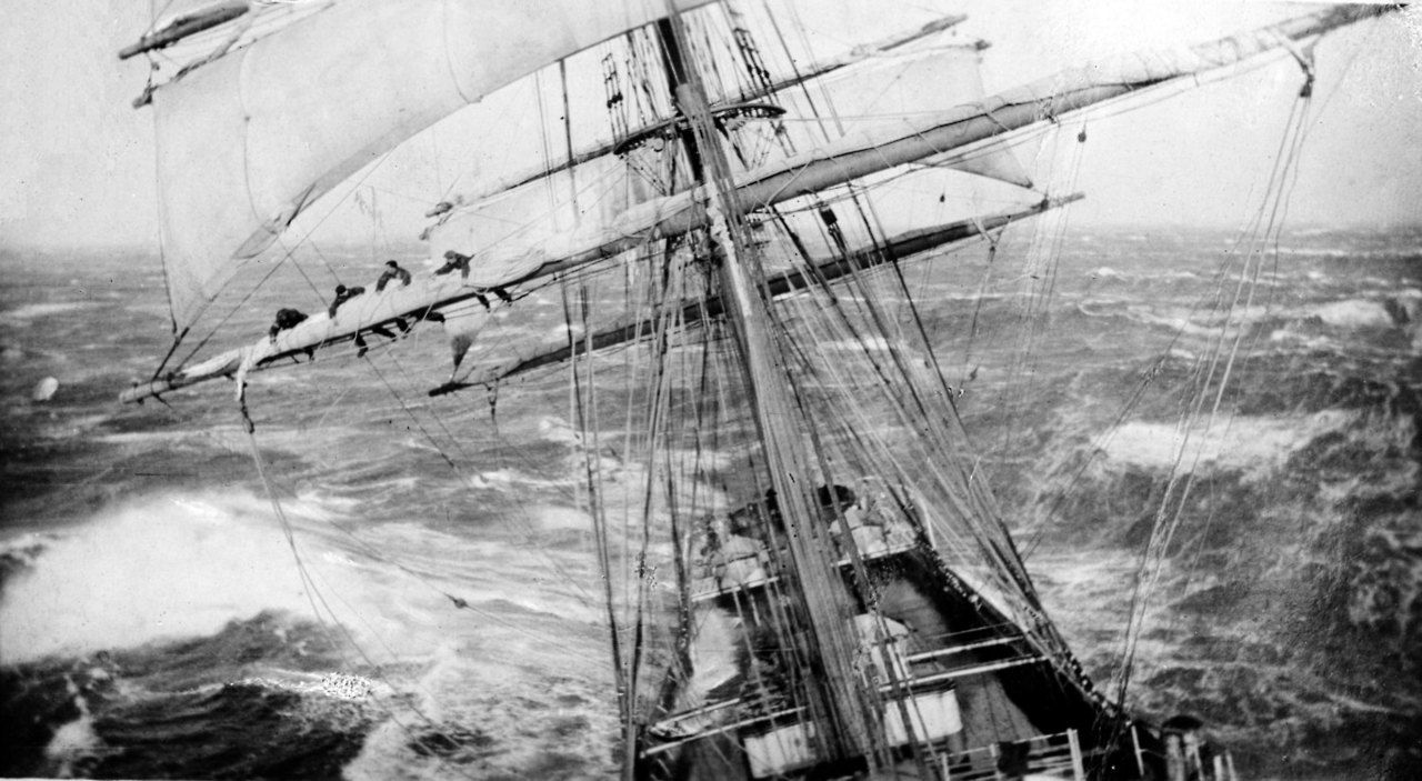 Vintage sailboat with sailors holding to mast in sea storm. Antique photo, ca. 1900′s / source: antiquephotoarchive