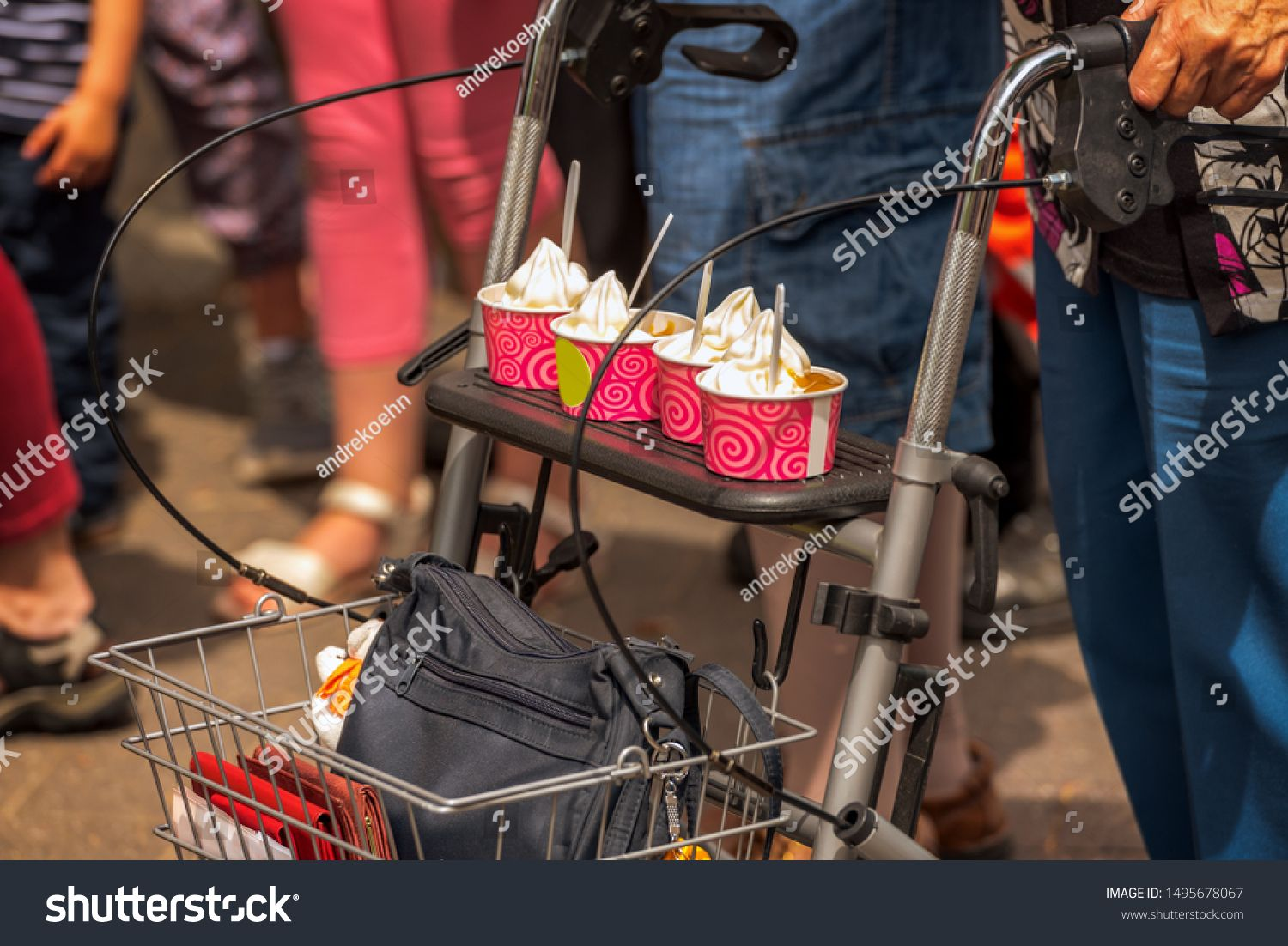 An old woman is driving on her wheeled walker yummy ice cream during a street party Concept food and drink