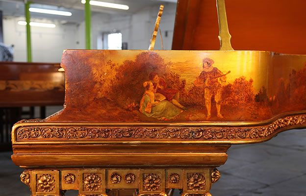 An art case, 1886, Steinway Model B grand piano with a gold case. Cabinet features hand paintings of cherubs and rural scenes of people playing musical instruments. Piano has ornately carved gate legs with four,ornately carved Corinthian pillars. Music desk has a beautiful scrolling filligree design with a central hand painted plaque.