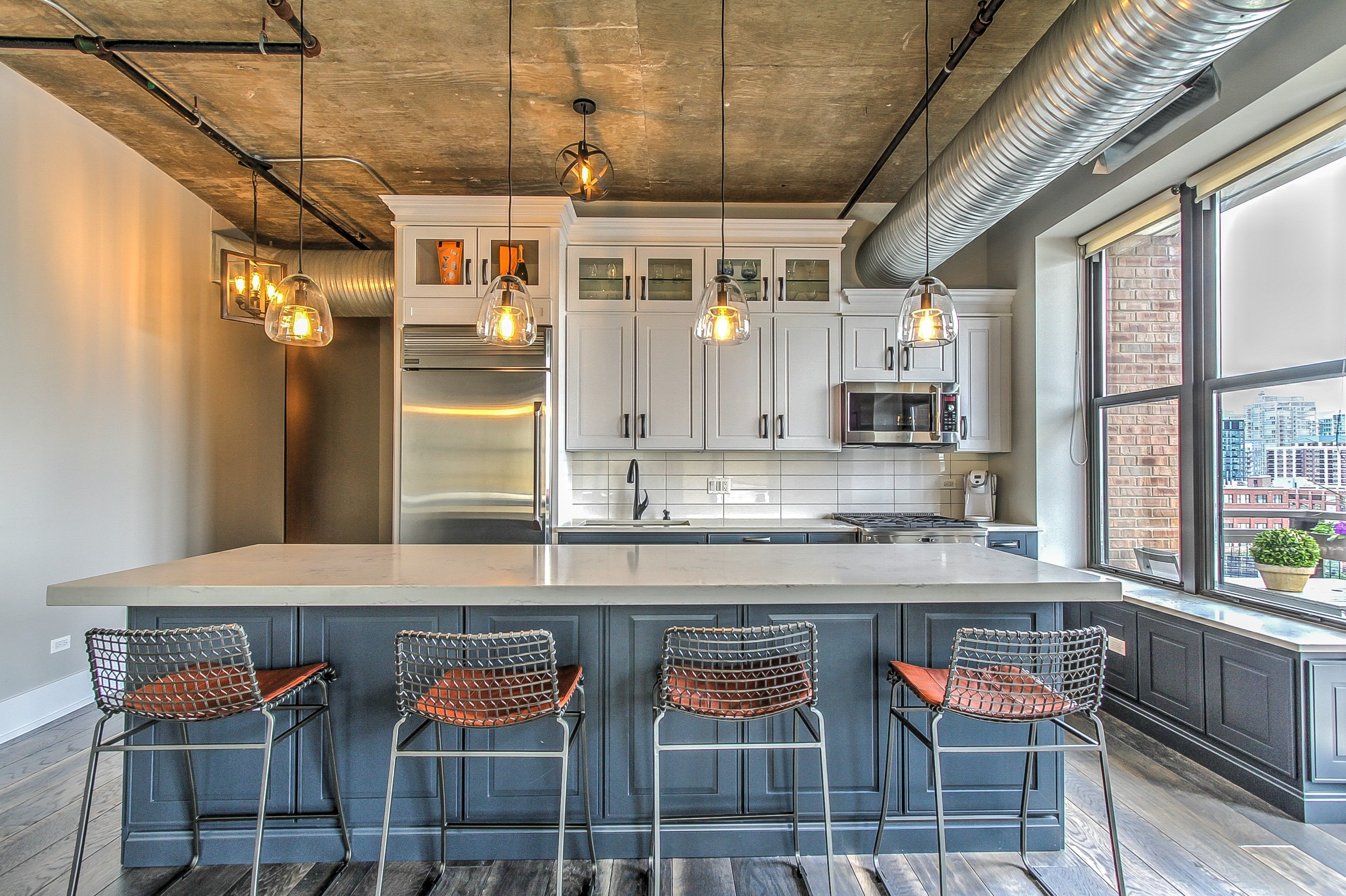 Who Said Industrial Spaces Have To Be Boring These White And Blue Cabinets By Echelon Make This Space Wholesale Kitchen Cabinets Kitchen Design Kitchen Trends
