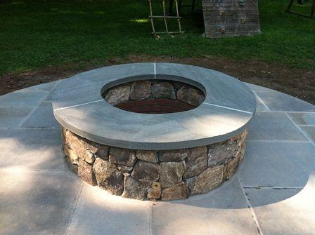 Outdoor raised circular gas fire pit with fieldstone veneer on bluestone  patio. - Outdoor Raised Circular Gas Fire Pit With Fieldstone Veneer On