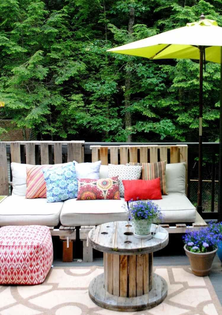 belle terrasse avec banc en palettes de bois et table en bobine decoree de coussins et pouf tabouret cool