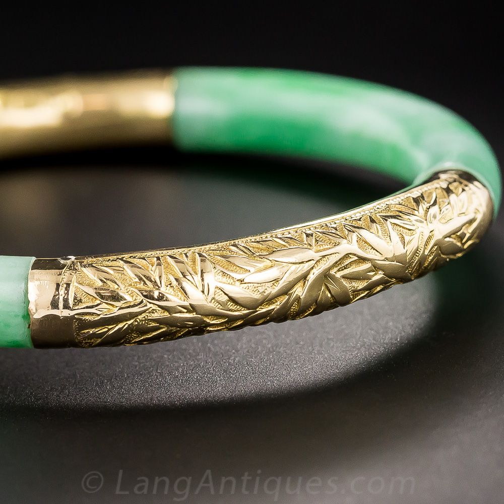 Jade and 18K Gold Bangle Bracelet, A matched pair of beautiful bright green jades hold hands with their 18K gold counterparts to create this exceptional vintage bangle bracelet. The 18K gold sections are hand engraved with a Chinese dragon and bamboo leaves, respectively. A solid bangle (no hinge).