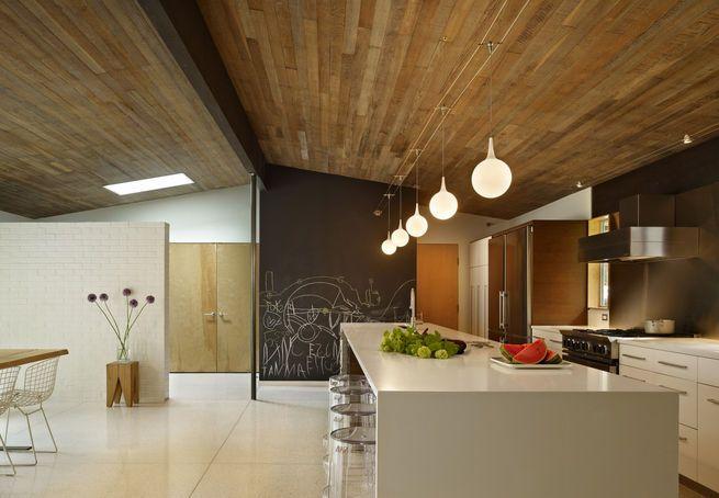 """Armarios de Ikea se combinaron con las superficies de trabajo duraderos y toques personales como un muro de pizarra.  Decopour suelo, un cemento de relleno similar al terrazo, es una superficie muy resistente, ideal para familias.  Cocina, comedor y el flujo de espacio al aire libre alrededor de un 12 pies de largo isla-apodado """"la madre de todas las islas"""" por parte de los residentes."""