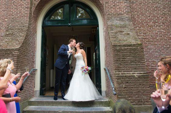 Net getrouwd paar proost samen met gasten op het bordes van de kerk