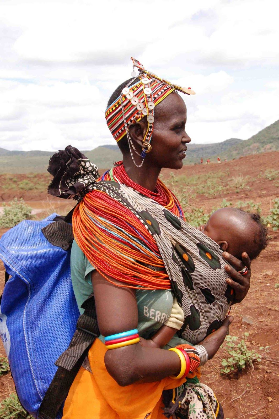 Partners for Care - A mother carrying a water pack and her baby