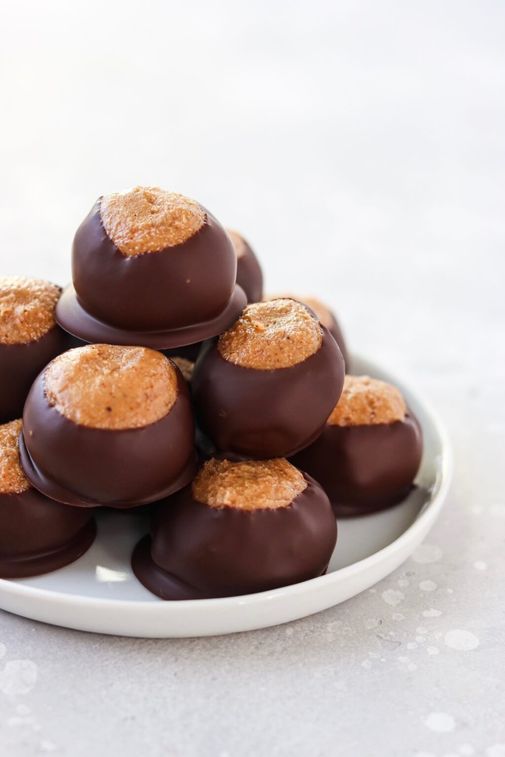 These Paleo Buckeye Balls are a gluten free, vegan, and dairy free version of the classic Christmas Cookie. Legume free as well! #christmas #holidays #cookies #cookieexchange #paleocookies #buckeyeballs #buckeyes #paleobuckeyes #paleochristmascookies #paleoholidayfood #holidaydesserts