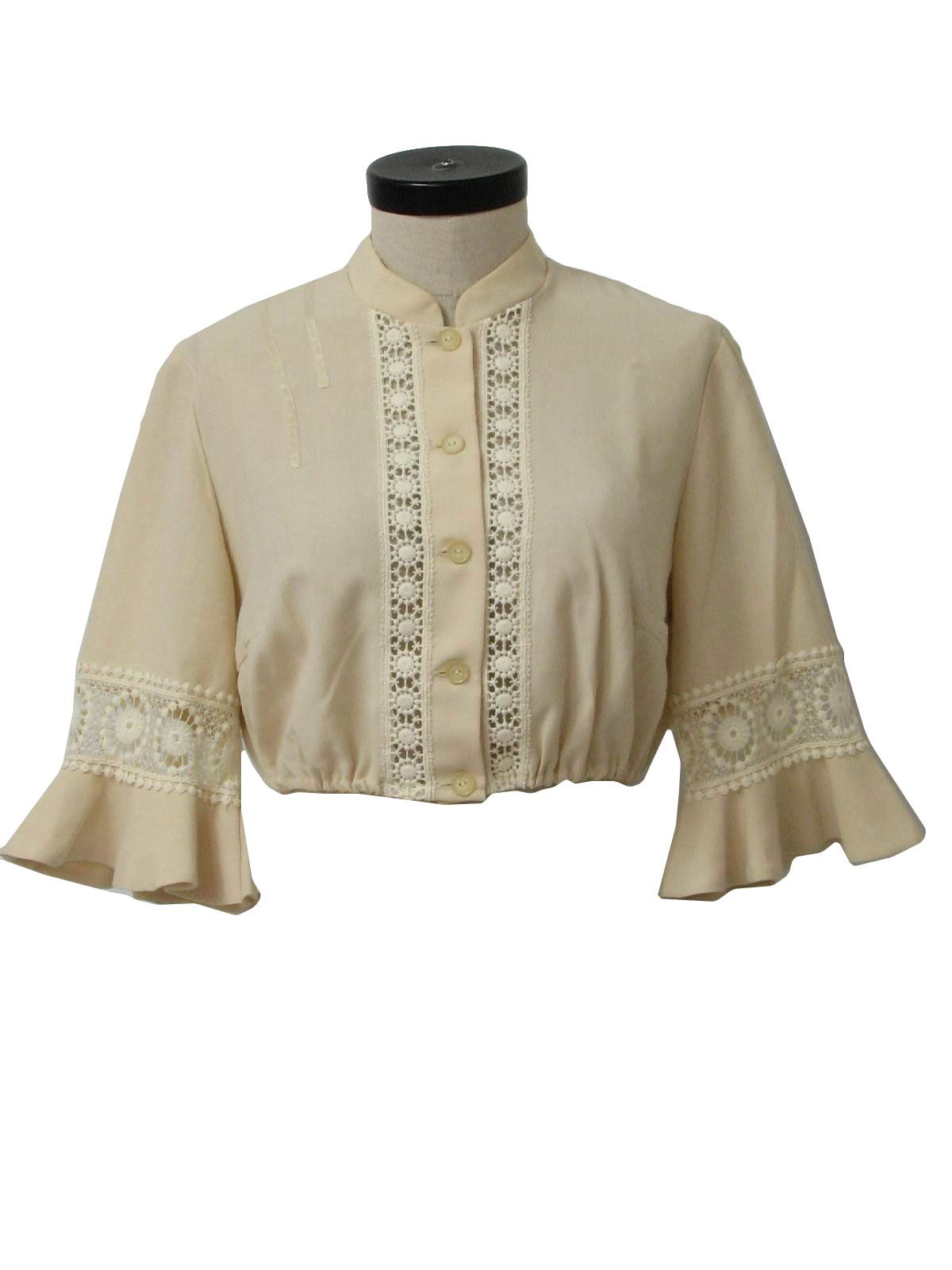 70s -Kuhnen- Womens ecru, blended cotton, half shirt, having set in longsleeves, which end below the elbow, having a 3.0in bell shaped band. Lace details each sleeve and flanks the front button close, below the band collar. French darts add bodice shaping, with elastic finishing the hem area. This garment measures 16in from shoulder to hem.