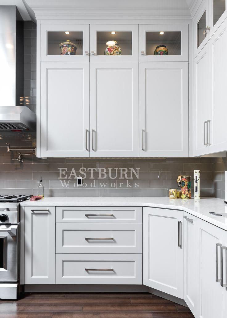 White kitchen cabinets with Top Knobs brushed nickel bar pulls. Open frame upper cabinets and shaker style doors.