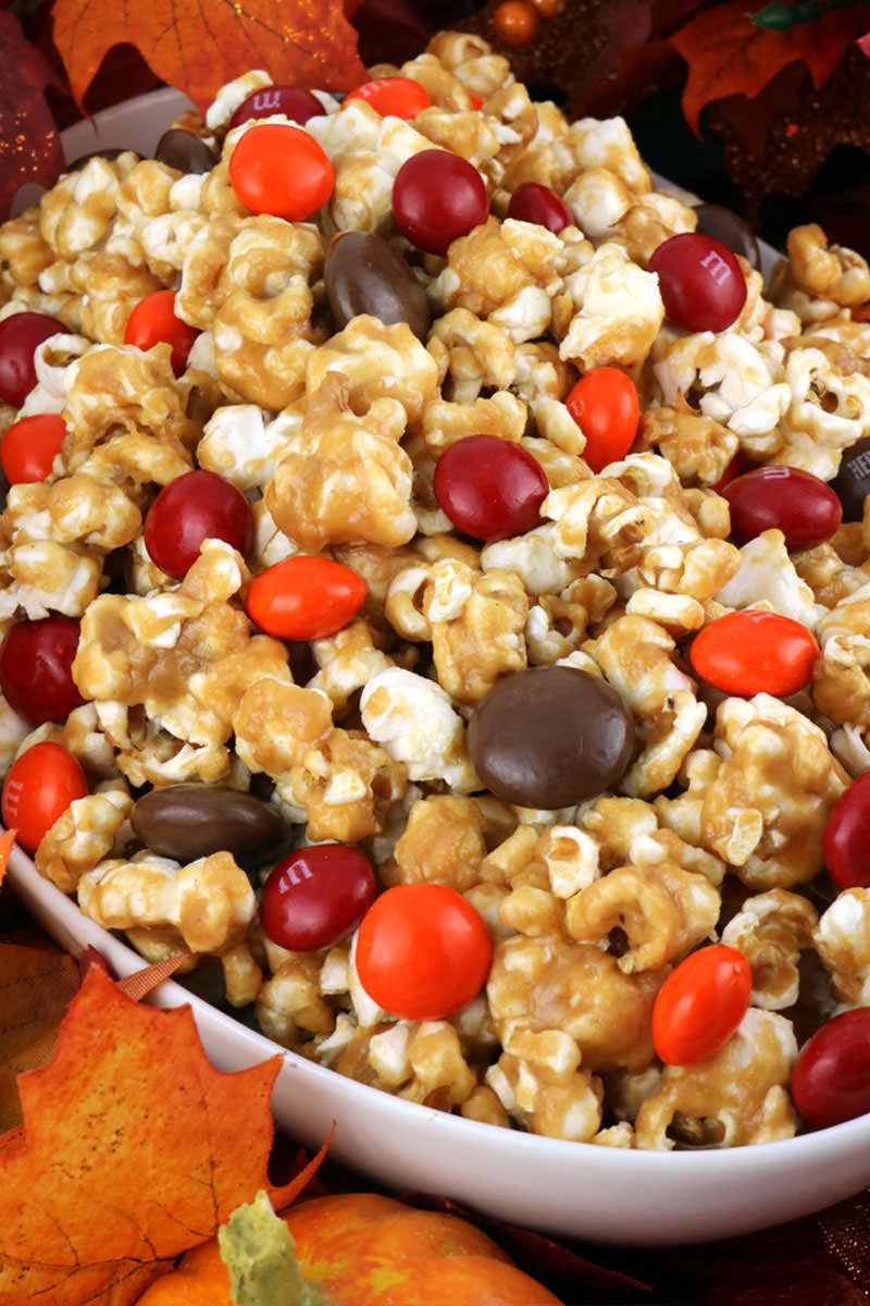 Peanut Butter Popcorn - sweet and salty popcorn covered in peanut butter and chock full of Peanut Butter M&M's. A delicious Peanut Butter dessert that is super easy to make! It would be a great Halloween Treat or a Fall movie night dessert! Pin this delicious popcorn recipe for later and follow us for more great Thanksgiving Food Ideas.