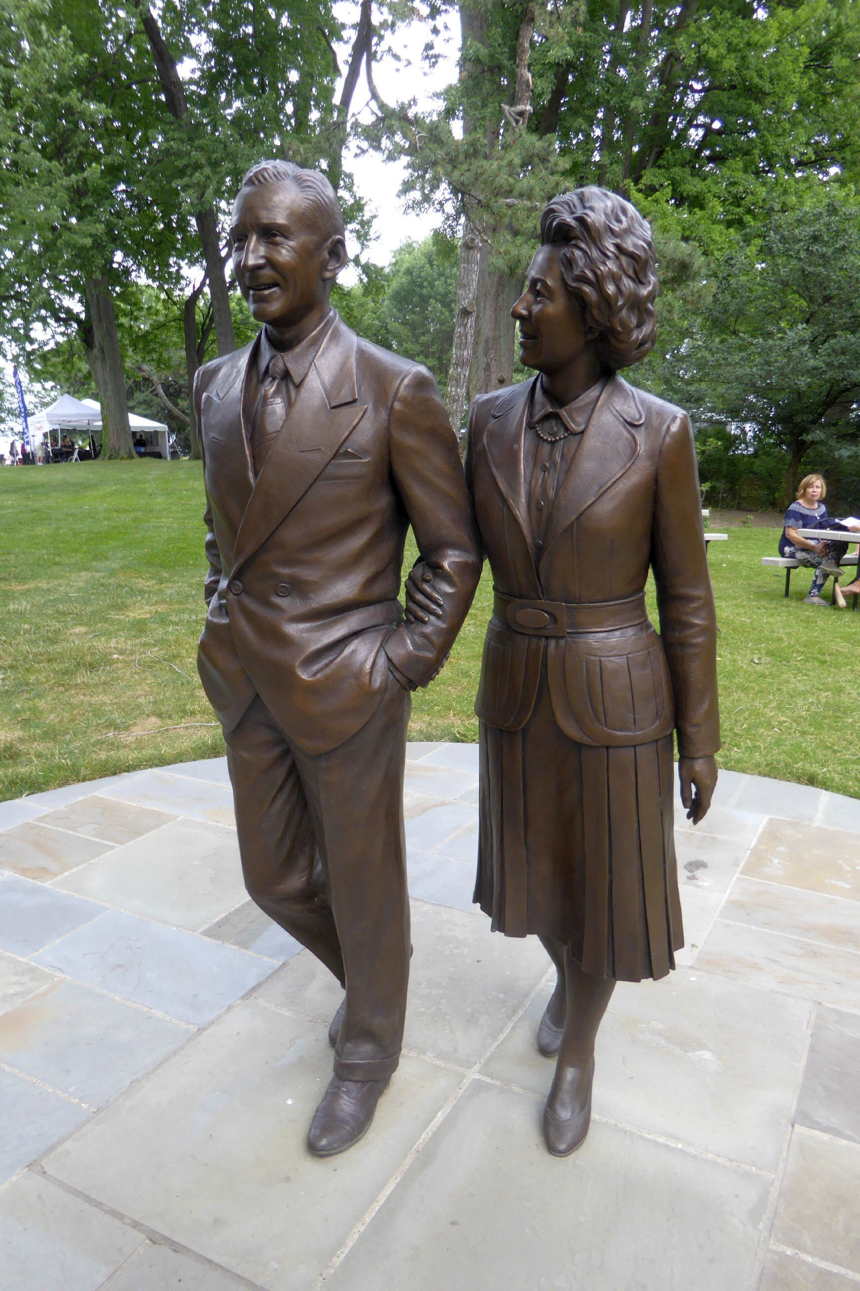 A Bronze Life Size Sculpture Of Edsel And Eleanor Walking Arm In