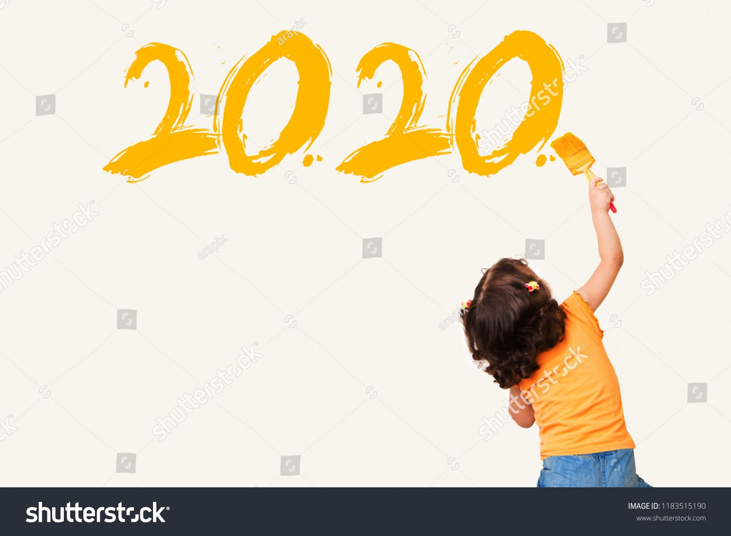 Cute little girl writing new year 2020 with painting brush