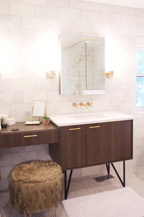 Vanity adorned with brass pulls topped with white quartz under ...