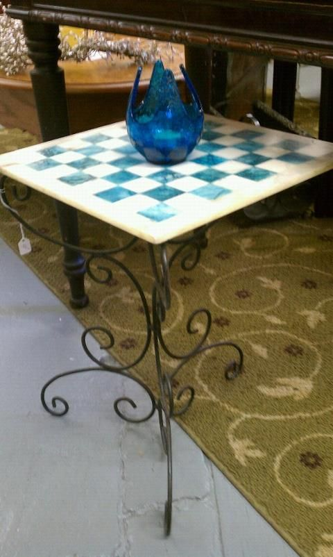 An Inlaid Marble Chess Board That Is Being Used As A Table