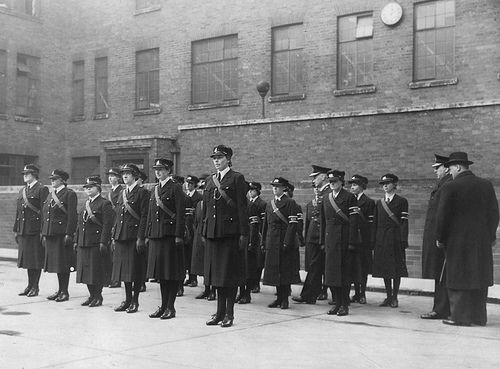 Manchester City Police's first six fully sworn female constables on parade in the yard of the force's headquarters in 1940. They are being inspected by their Chief Constable Sir John Maxwell.  They are joined by members of the Women's Auxiliary Police Corp, who are denoted by their wearing armbands. Members of the corps did not have police powers. http://www.gmpmuseum.com