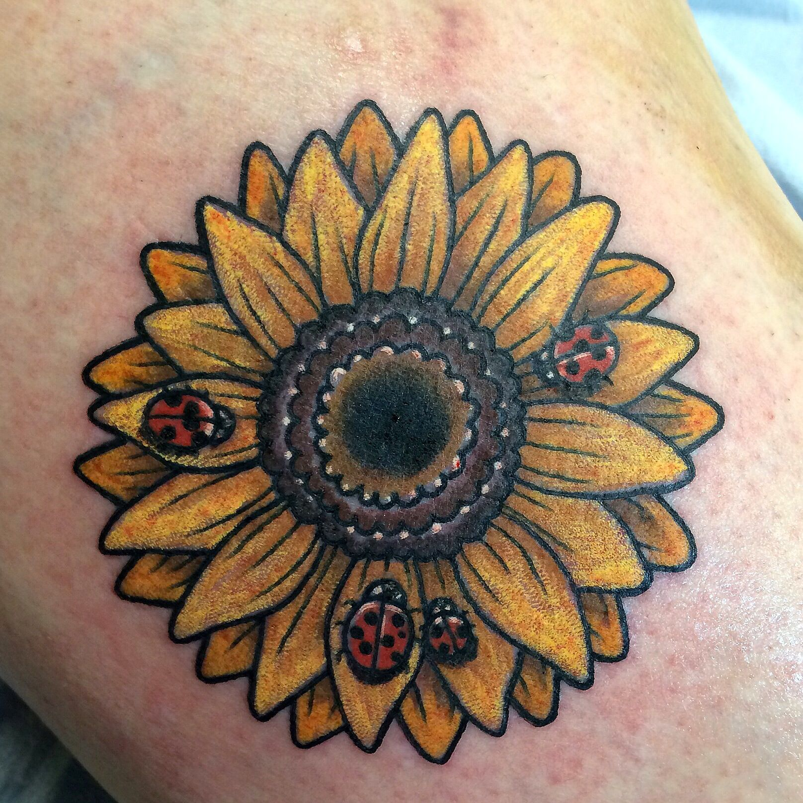 Photo of Sunflower with ladybugs tattoo. By Brandy Pouliot at Twisted Anchor Tattoo in Oc…