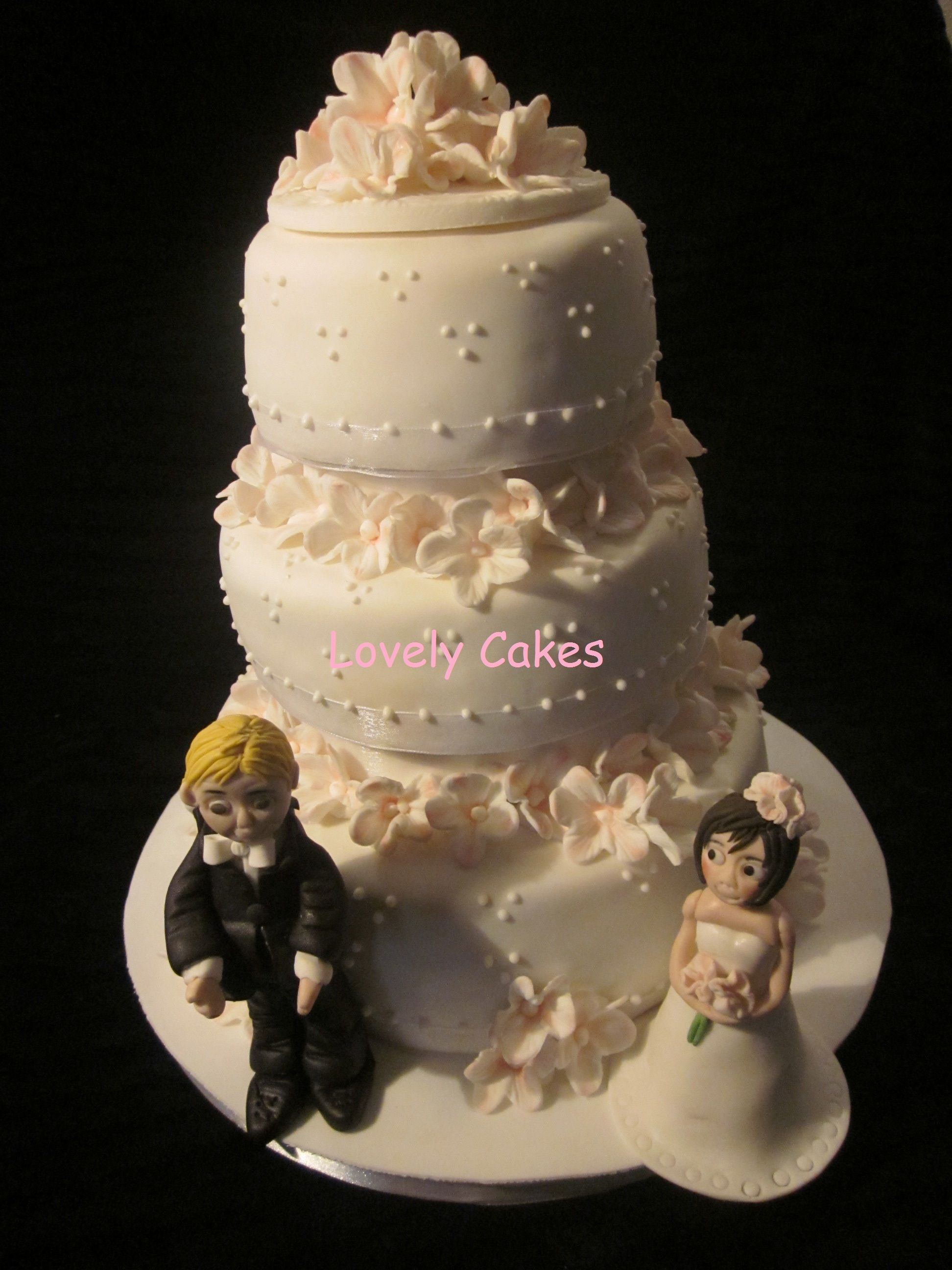Tarta de boda en tres pisos con petunias y pareja de novios