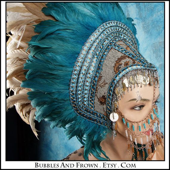 This is another very eye catching piece. This is very busy with a lot going on unlike others, which does not appeal to me as much. This headpiece comes over the face with beads and jewels, with a sense of Indian/Bollywood style. Blue feathers are used which make the piece bold and stand out, however they lie above a bed of pale brown feathers. The colour of these feathers link in with pieces from the front of the headpiece. All the colours tie in very well. Different patterns are used…