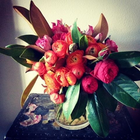 High and tight bouquet with color blocked Rununculus and Magnolia leaves.